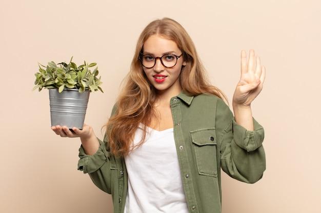 Blondynka uśmiechnięta i wyglądająca przyjaźnie, pokazująca cyfrę cztery lub czwarte z ręką do przodu, odliczająca