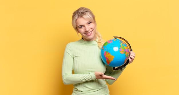Blondynka uśmiechnięta radośnie, czując się szczęśliwa i pokazując koncepcję w przestrzeni kopii z dłoni