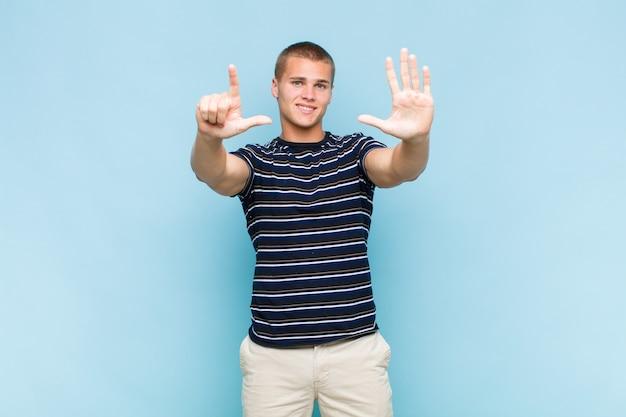 Blondynka uśmiechnięty i wyglądający przyjaźnie, pokazujący numer siedem lub siódmy z ręką do przodu, odliczający