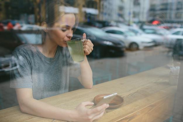Blondynka używa telefonu. dziewczyna i smartfon. kobieta siedzi w kawiarni z komórką.