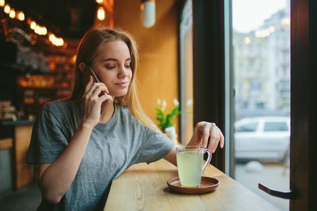 Blondynka używa telefonu. dziewczyna i smartfon. kobieta siedzi w kawiarni z komórką