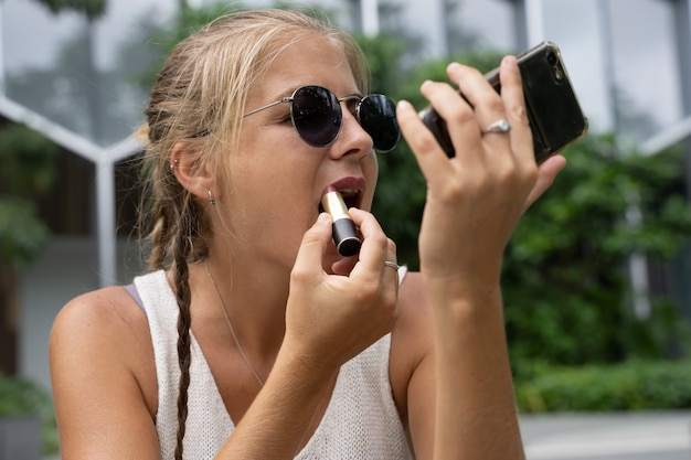 Blondynka używa telefonu komórkowego jako lustra, podczas gdy sama się składa