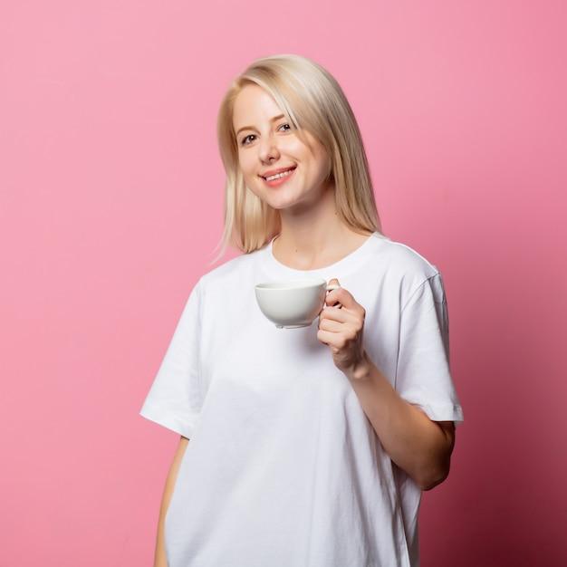 Blondynka w białej koszulce z filiżanką kawy