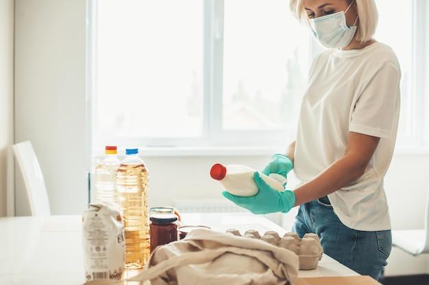 Blondynka w białej koszuli i dżinsach rozpakowuje produkty kupione w internecie