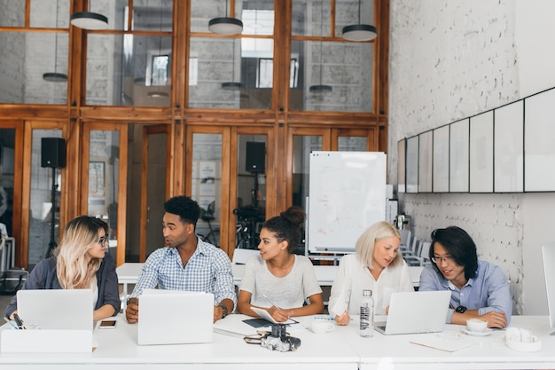 Blondynka w białej koszuli rozmawia z azjatyckim przyjacielem i pije kawę w pobliżu laptopa z flipchartem. niezależni projektanci stron internetowych pracujący razem w sali konferencyjnej i korzystający z komputerów.