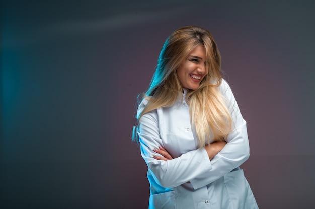 Blondynka w białej koszuli wygląda uwodzicielsko i pozytywnie.