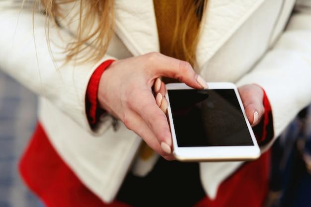 Blondynka w białej kurtce robi zdjęcie na swoim telefonie