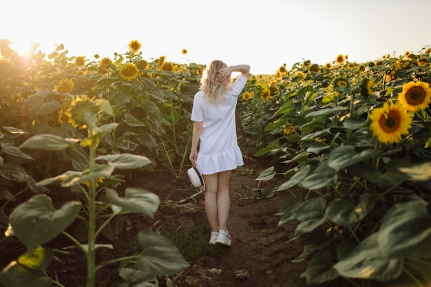 Blondynka w białej sukni na polu słoneczników