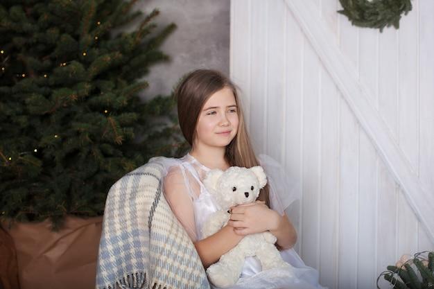 Blondynka w białej sukni siedzi na krześle w objęciach z misiem i marzeniami. przytulny dom pokój w stylu ekologicznym w zgodzie z naturą. świąteczna atmosfera, komfort.