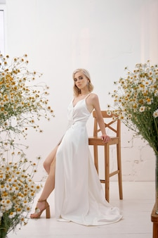 Blondynka W Białej Sukni ślubnej Stojąca W Domu Wśród Bukietów Polnych Kwiatów Premium Zdjęcia