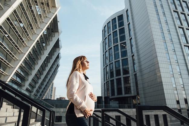 Blondynka w ciąży w swobodnym stylu. w wielkim mieście. 9 miesięcy oczekiwania. na tle miasta i wysokich budynków.
