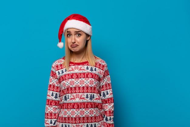 Blondynka w czapce mikołaja czuje się smutna i jęcząca z nieszczęśliwym spojrzeniem, płacze z negatywnym i sfrustrowanym nastawieniem