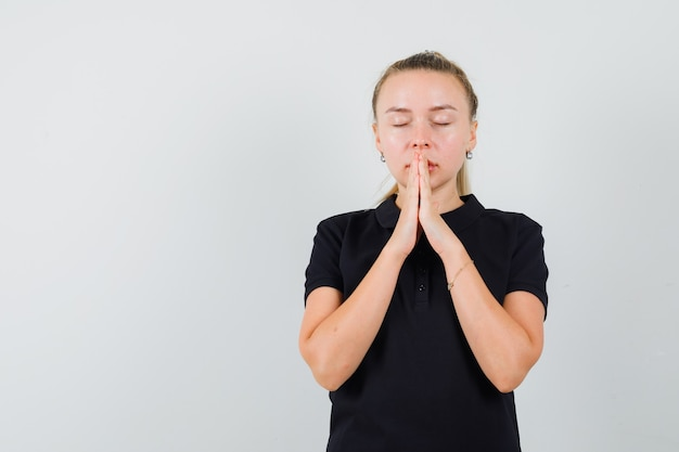 Blondynka w czarnej koszulce modli się i zamyka oczy i wygląda na zrelaksowaną