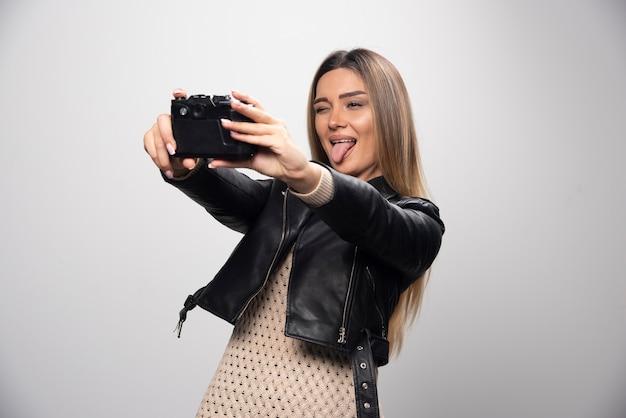 Blondynka w czarnej skórzanej kurtce, biorąc jej selfie z aparatem.