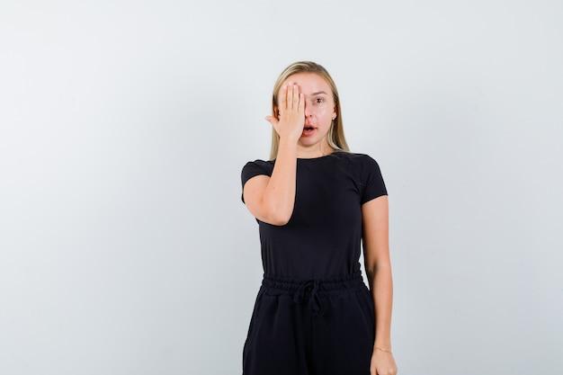 Blondynka w czarnej sukience trzymająca rękę na oku i wyglądająca na zdumioną, widok z przodu.