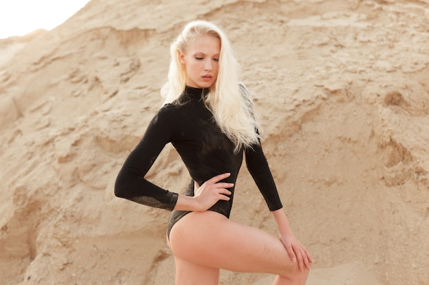 Blondynka w czarnym body slim pozowanie w piasku ziemi.
