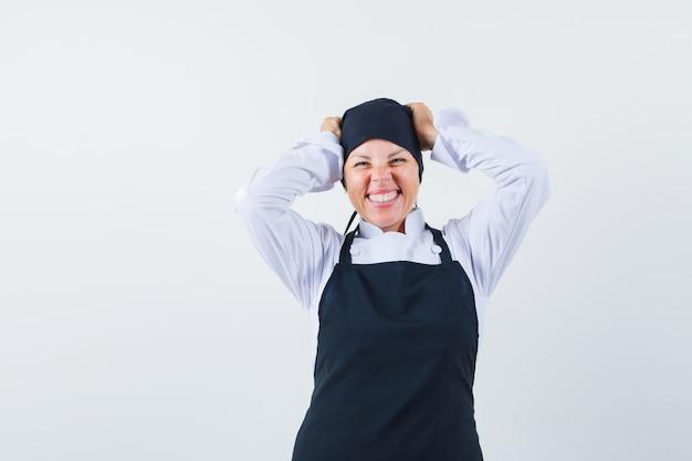 Blondynka w czarnym mundurze kucharza trzymając się za ręce na głowie, krzywiąc się i uśmiechając się wdzięcznie i ładnie wyglądając