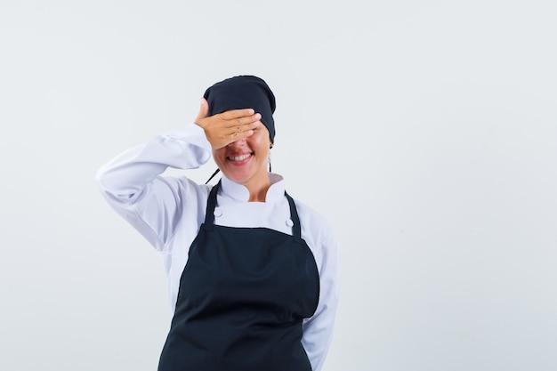 Blondynka w czarnym mundurze kucharza zakrywającego oczy rękami i patrząc nieśmiało