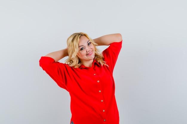 Blondynka w czerwonej bluzce kładąc ręce za głowę i patrząc ładnie, widok z przodu.