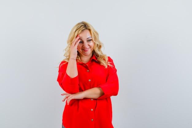 Blondynka w czerwonej bluzce kładzie rękę na głowie, myśli o czymś i ładnie wygląda, widok z przodu.