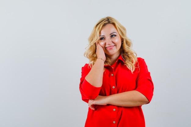 Blondynka w czerwonej bluzce, opierając policzek na dłoni, pozowanie na kamery i patrząc szczęśliwy