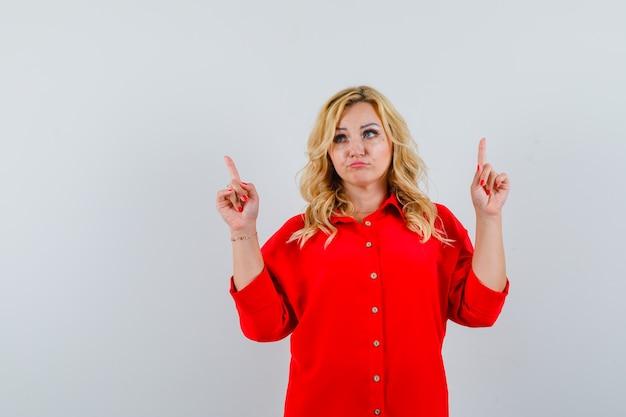 Blondynka w czerwonej bluzce skierowana w górę palcami wskazującymi, odwracająca wzrok i zamyślona, widok z przodu.