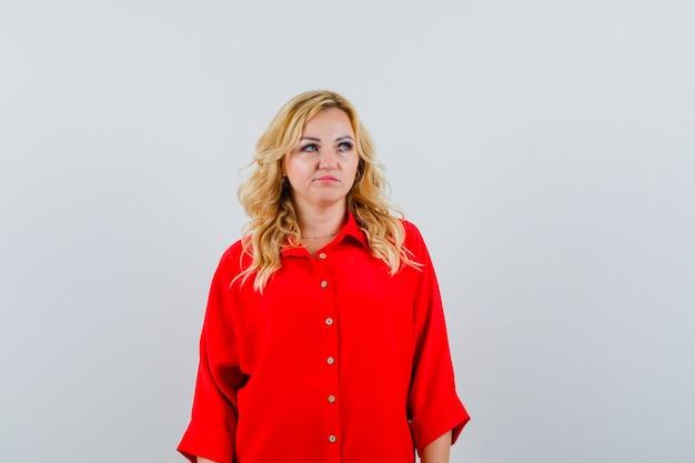 Blondynka w czerwonej bluzce, stojąc prosto i pozowanie na kamery i patrząc poważnie