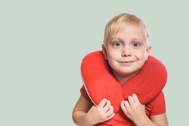 Blondynka w czerwonej koszulce z poduszką podróżną