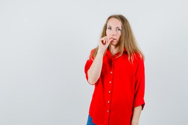Blondynka w czerwonej koszuli gryzie paznokieć i wygląda zamyślona