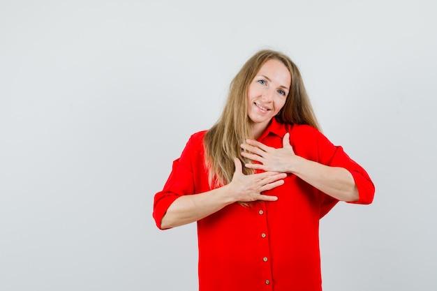 Blondynka w czerwonej koszuli trzymająca się za ręce na piersi i wyglądająca na wdzięczną,