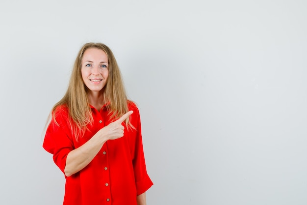 Blondynka w czerwonej koszuli wskazująca na prawy górny róg i wyglądająca wesoło,