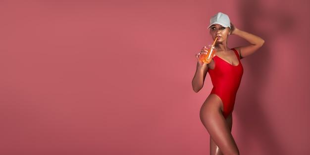 Blondynka w czerwonym body lub kostiumie kąpielowym i czapce na kolorowym różu