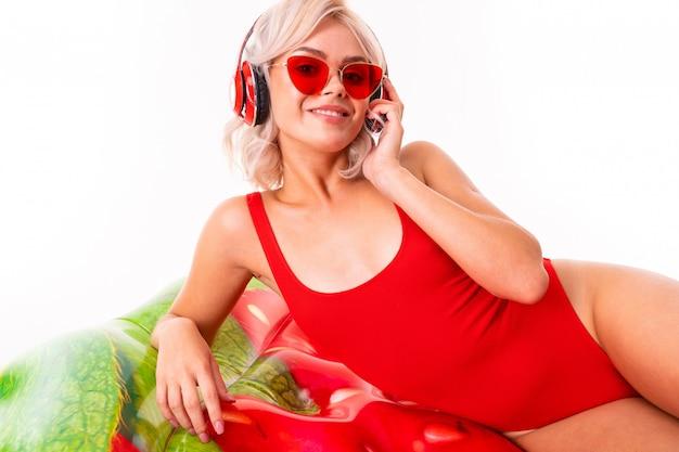 Blondynka w czerwonym kostiumie kąpielowym i okularach przeciwsłonecznych leży na materacu i słucha muzyki na słuchawkach