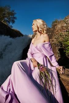 Blondynka w długiej różowej sukience siedzi na kamieniu w pobliżu wodospadu