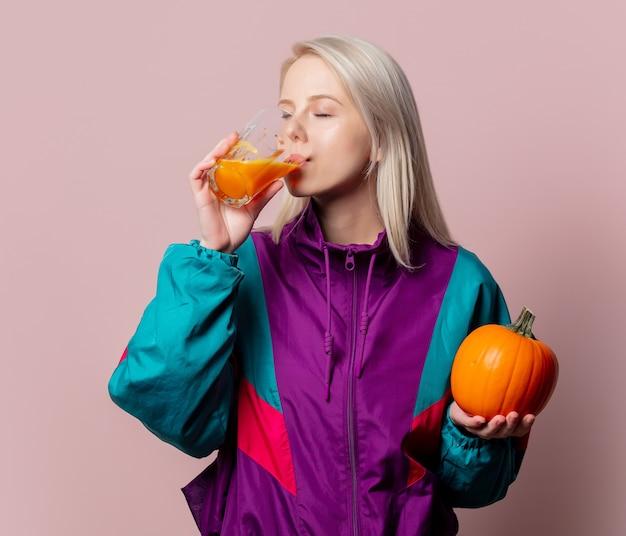 Blondynka w dresie lat 90. z sokiem dyniowym w szkle na różowo