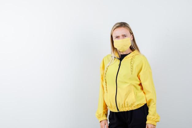 Blondynka w dresie, maska, patrząc na kamery i wyglądająca na nerwową, widok z przodu.