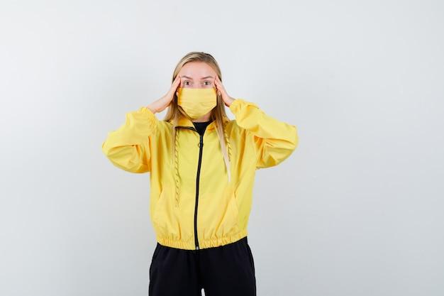 Blondynka w dresie, z maską trzymająca się za ręce na skroniach i zdziwiona, widok z przodu.