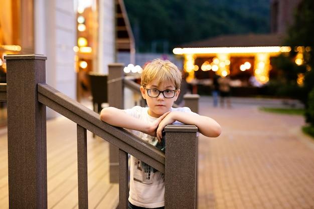 Blondynka w dużych okularach chodzenie na zewnątrz wieczorem