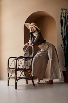 Blondynka w dużym słomkowym kapeluszu opierając się na rattanowym krześle