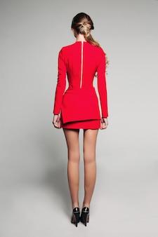 Blondynka w eleganckiej czerwonej sukience i wysokich obcasach.
