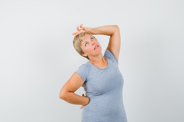 Blondynka w jasnoniebieskiej koszulce trzyma jedną rękę na pasie, myśli o czymś i patrzy w górę i patrzy w zamyśleniu, widok z przodu.