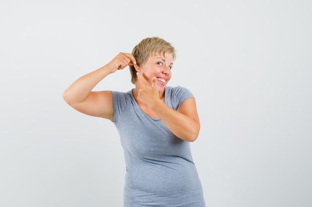 Blondynka w jasnoniebieskiej koszulce, wskazując na zęby, uszy i próbując coś usłyszeć, patrząc wesoło, z przodu.