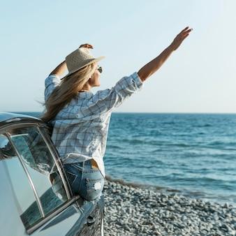 Blondynka w kapeluszu i okularach przeciwsłonecznych, stojąc z okna samochodu