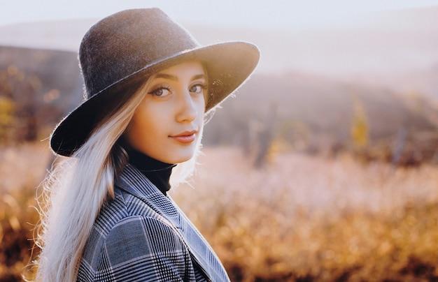 Blondynka w kapeluszu pozowanie w polu i patrząc na kamery podczas pięknego zachodu słońca