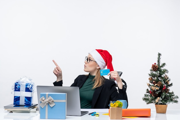 Blondynka w kapeluszu świętego mikołaja i okularach siedzi przy stole trzymając prezent na boże narodzenie i kartę bankową w biurze