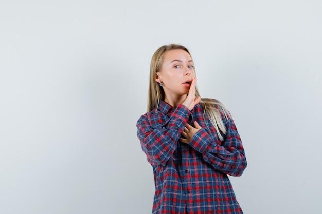 Blondynka w koszuli dorywczo mówi tajemnicę za ręką, widok z przodu.