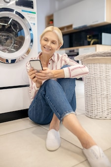 Blondynka w koszuli w paski siedzi obok pralki i czyta coś w internecie