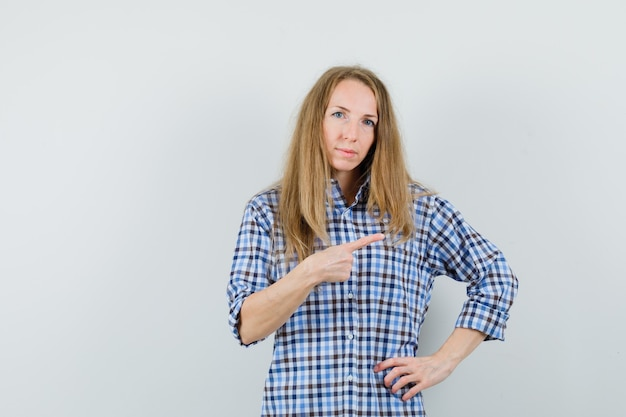Blondynka w koszuli wskazująca na prawy górny róg i wyglądająca na pewną siebie,