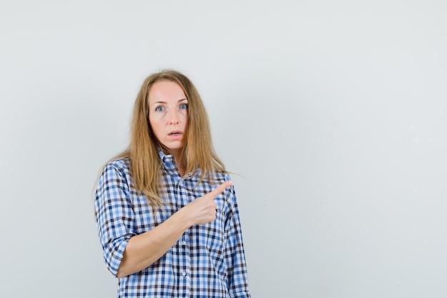Blondynka w koszuli wskazująca na prawy górny róg i wyglądająca na zdziwioną,