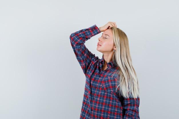 Blondynka w kraciastej koszuli kładąc rękę na głowie i pozowanie na kamery i patrząc atrakcyjny, przedni widok.